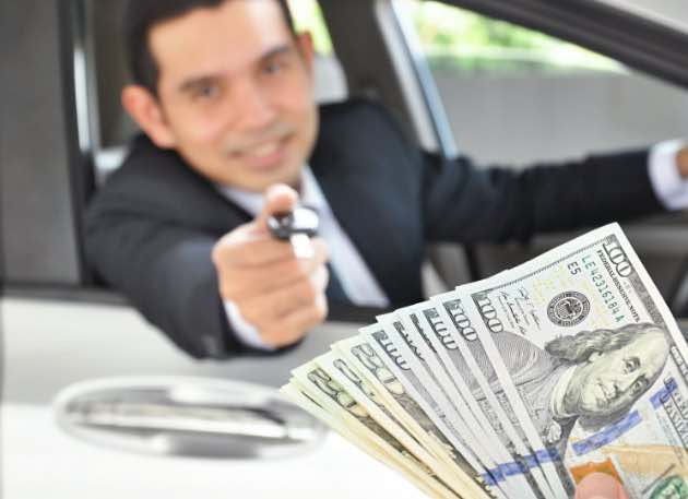 Dollars bills and one men showing car keys in a car