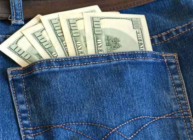 Hundred dollars bills in jean back pocket